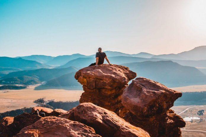 man sitting on a boulder