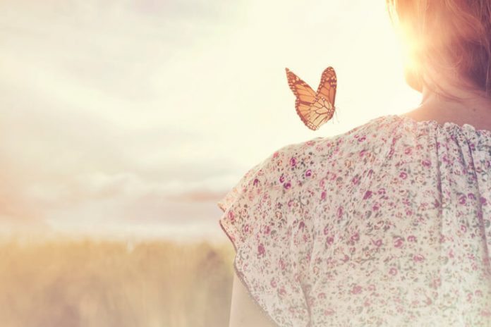 monarch butterfly on woman with sunrise