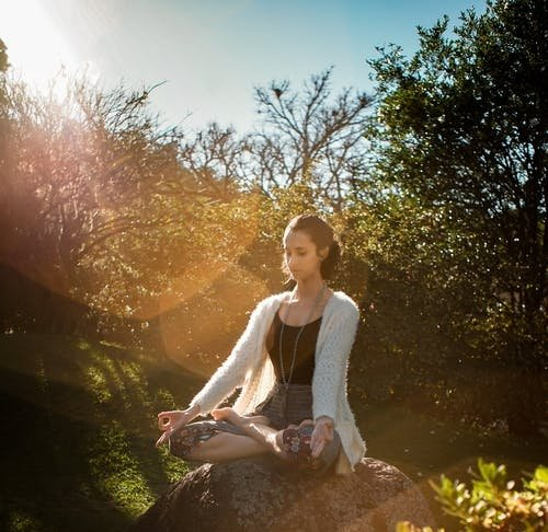 woman meditating on a rock with the sun shining