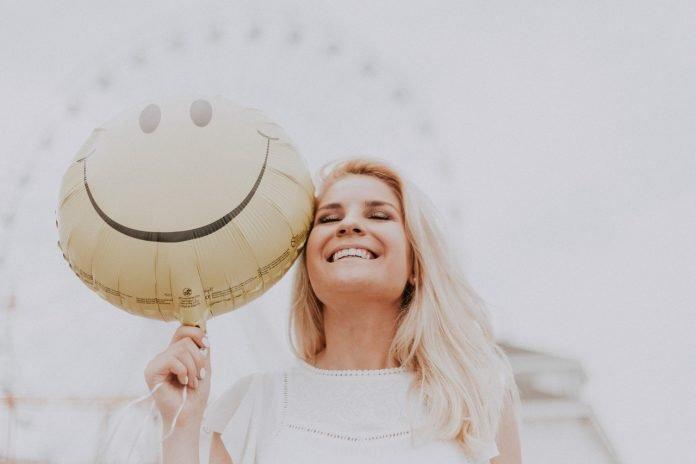 happy woman holding smiley balloon